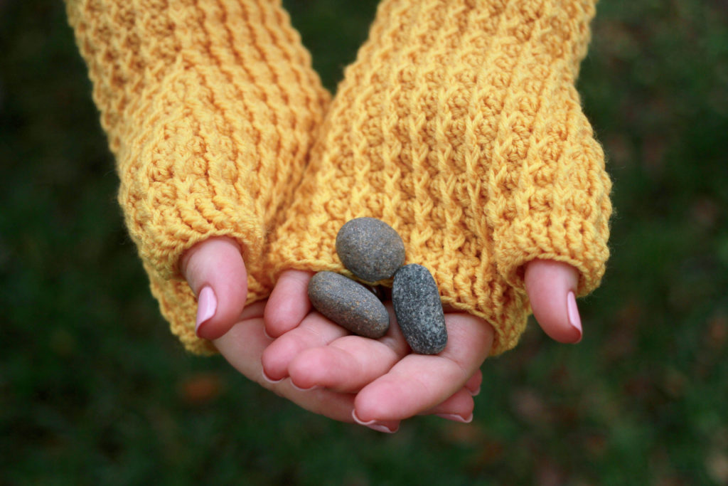 Woman holding rocks wearing yellow fingerless mitts: Rails Mitts