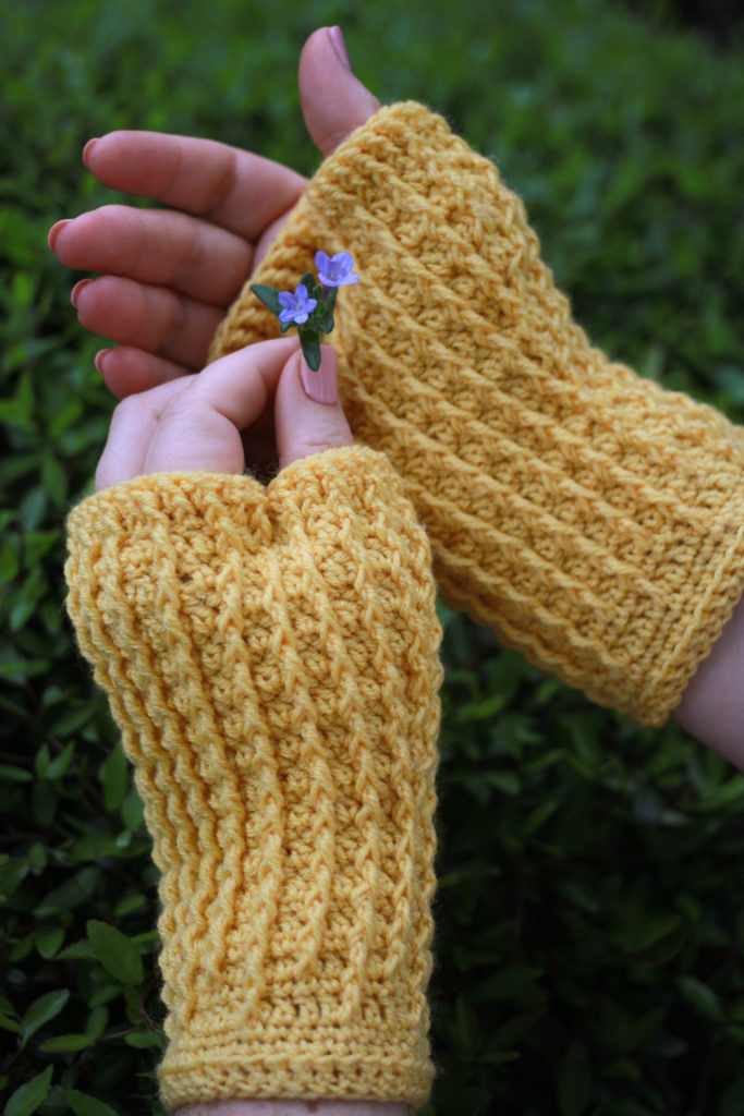 Woman holding small purple flower wearing yellow fingerless mitts: Rails Mitts