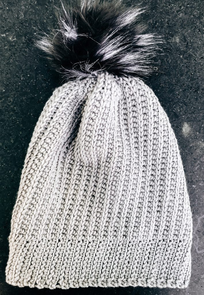 Grey beanie with large, black, faux fur pom pom lying flat on black granite surface.