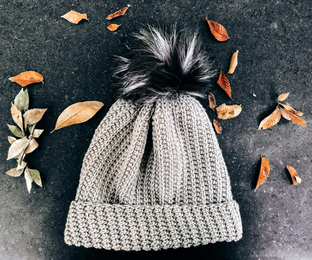 Grey hat with large, black, faux fur pom pom laying on a black granite surface with fallen, tan leaves placed around.