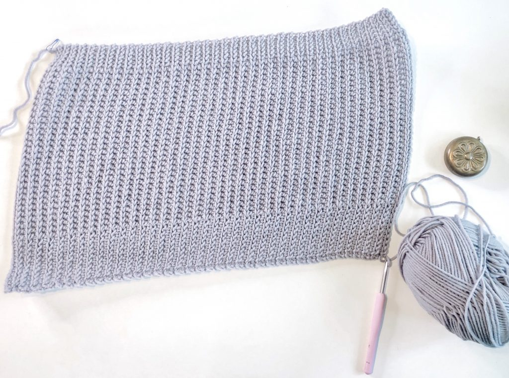 Grey rectangle of crocheted fabric with tape measure, crochet hook, and  ball of grey yarn to side.