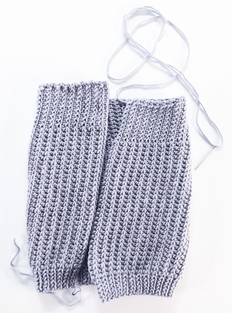 Grey rectangle of crocheted fabric, folded with ends meeting in center to show placement of seam.