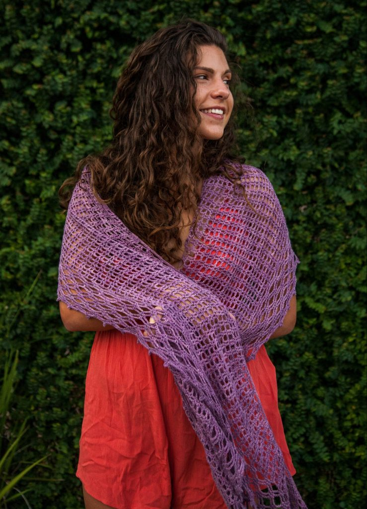 Lady standing against brick wall wearing an orange jumper and the gridlock shawl in purple